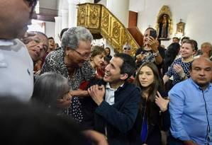 Guaidó é cumprimentado por apoiadora ao lado da sua mulher (à direita), Fabiana Rosales Foto: LUIS ROBAYO / AFP
