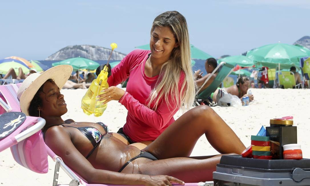 Daniele Araújo hidrata a pele de uma cliente que fez a marquinha de fita isolante na Praia do Leblon Foto: Fábio Guimarães