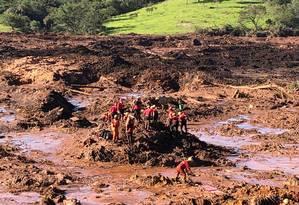 Bombeiros trabalham no resgate de corpos de veículo soterrado pela lama Foto: Márcia Foletto / Agência O Globo