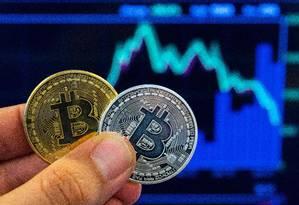 Grupos possuem esquemas para resgatar moedas virtuais em dinheiro Foto: JACK GUEZ / AFP