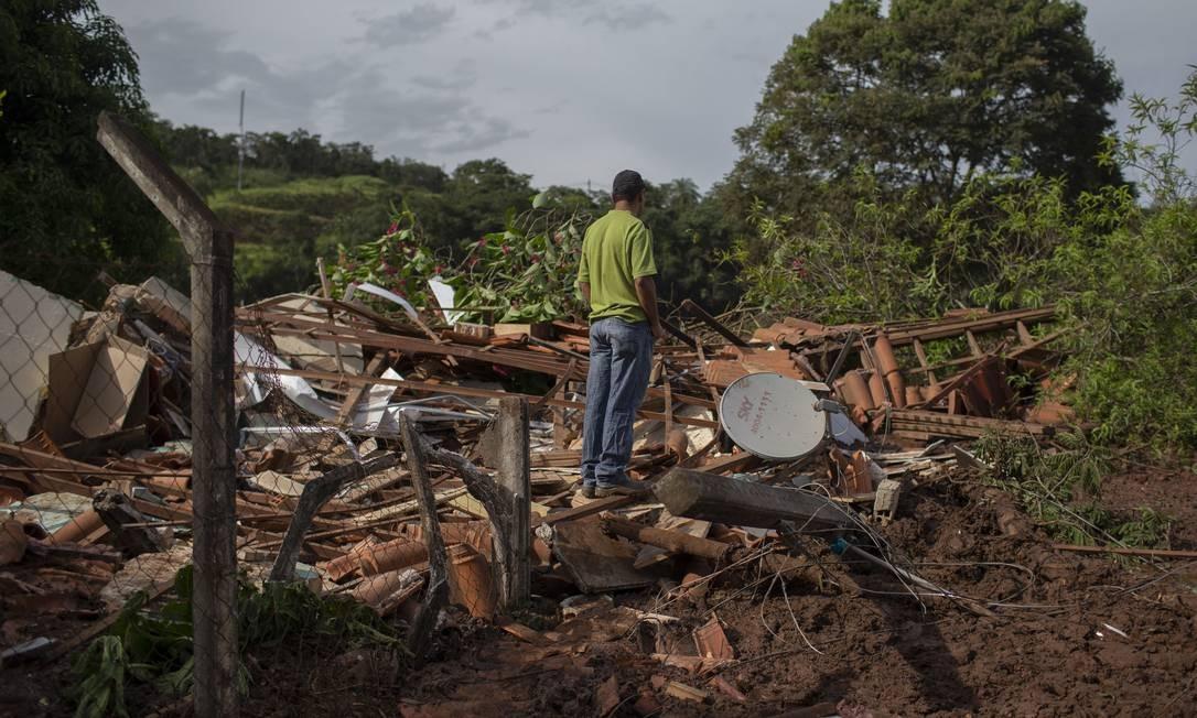 Moradores da comunidade Parque da Cachoeira olham os destroços de suas casas após o rompimento da barreira Foto: Mauro Pimentel / AFP