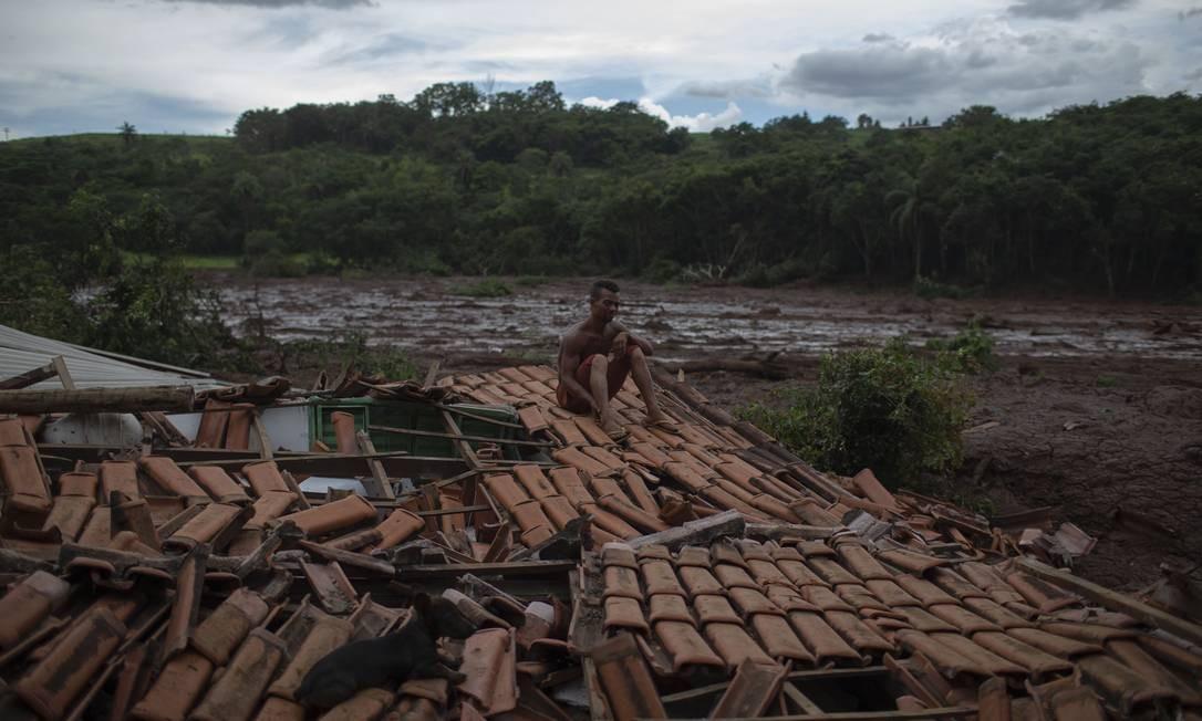 """""""Tudo tremeu. Vi árvores gigantes e pessoas desaparecendo sob a lama"""", conta Emerson dos Santos, sentado sobre o telhado de sua casa para proteger o que sobrou de saqueadores. Foto: Mauro Pimentel / AFP"""