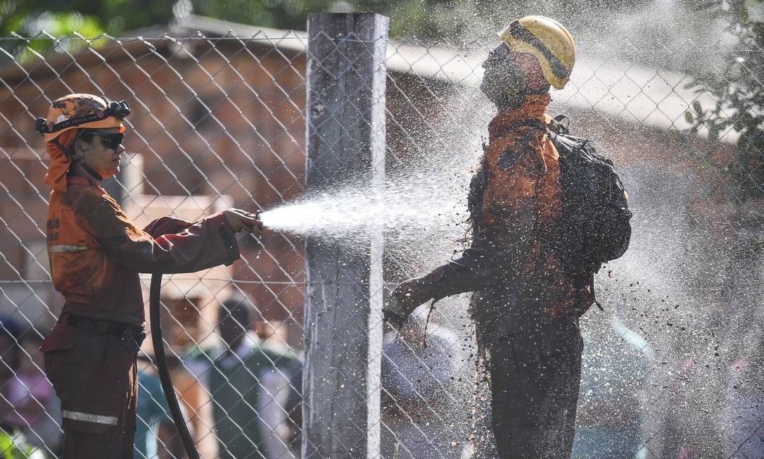 Bombeiros se limpam após tentativas de resgate na área devastada Foto: Pedro Vilela / Getty Images
