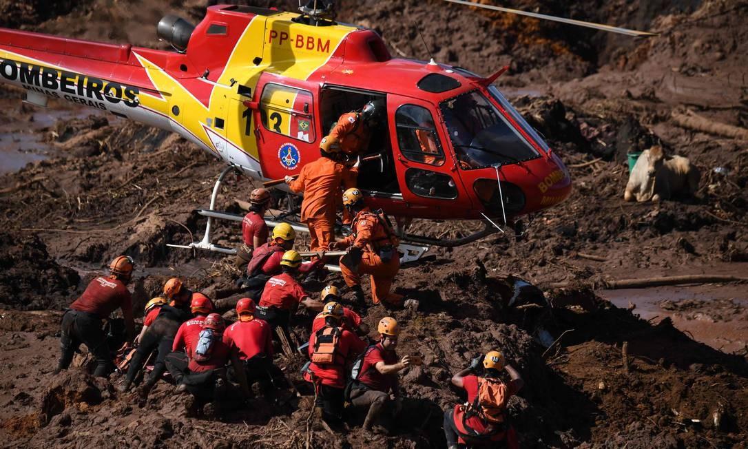 Bombeiros resgatam corpos com helicóptero na área atingida pelo rompimento da barragem Foto: MAURO PIMENTEL / AFP