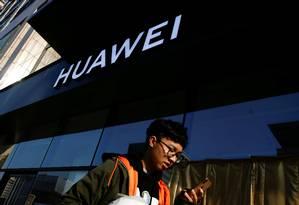 Homem passa por loja da Huawei em Pequim: processos nos EUA Foto: Thomas Peter / REUTERS