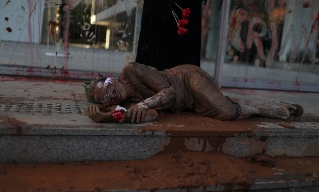 Integrante do ato vendada e deitada no chão, suja de lama Foto: PILAR OLIVARES / REUTERS