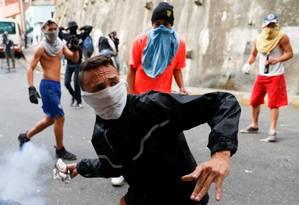 Manifestante arremessa de volta cilindro de gás contra forças policiais venezuelanas Foto: Carlos Garcia Rawlins / REUTERS
