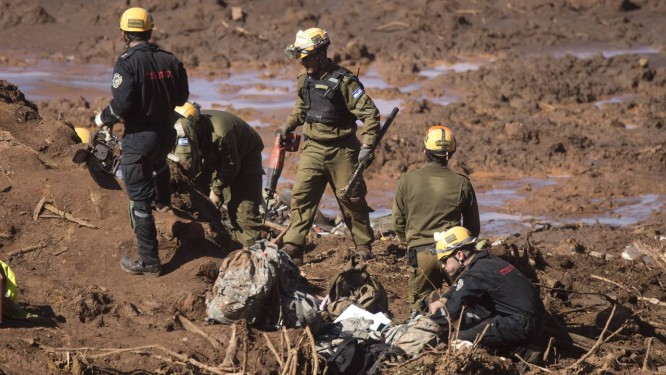 Soldados israelenses (de preto) trabalham junto a bombeiros de Minas Gerais na região onde um micro-ônibus foi encontrado soterrado 29/01/2019 Foto: Márcia Foletto / Agência O Globo