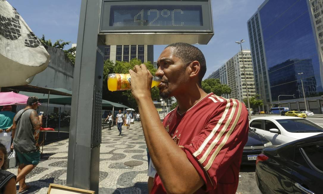 Na Avenida Presidente Vargas, no centro do Rio, homem se refresca com suco para amenizar o calorão de 42°C registrados pelo termômetro. Foto: Gabriel de Paiva / Agência O Globo