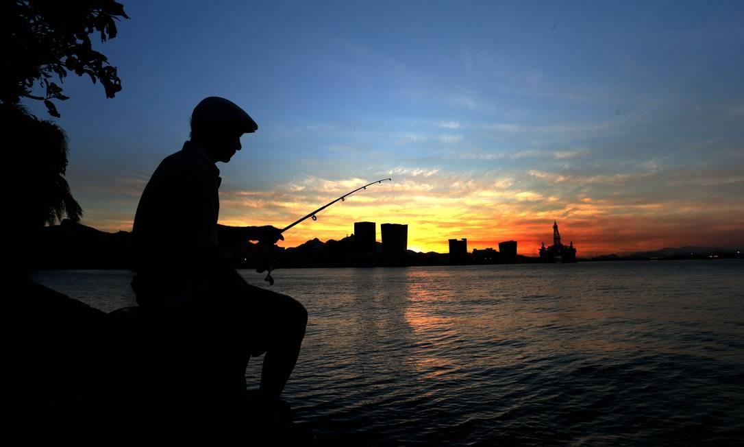 Equanto o sol se despede no fim de tarde, o aposentado Josué Menezes, 82 anos, aproveita o visual da Baía de Guanabara pescando ao lado do Museu do Amanhã, na Praça Mauá. Foto: Marcio Alves / Agência O Globo