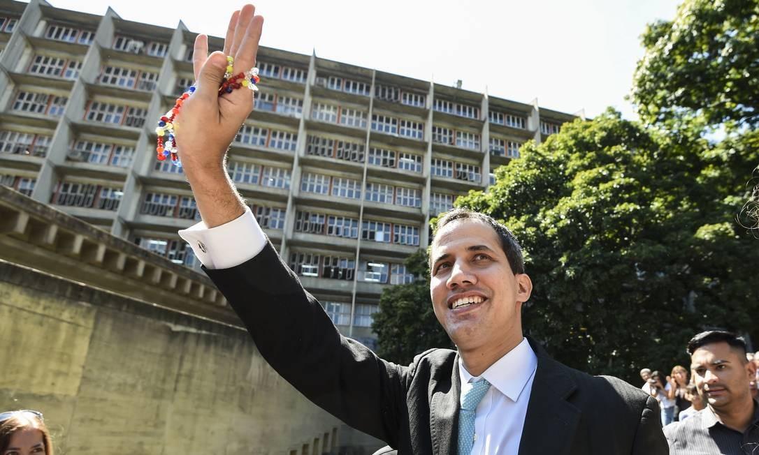 Líder opositor Juan Guaidó acena para apoiadores em universidade de Caracas Foto: JUAN BARRETO / AFP