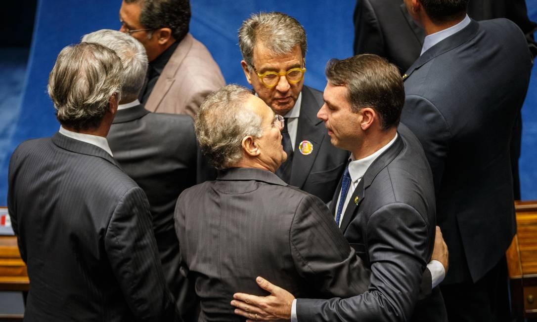 O senador Renan Calheiros (MDB-AL), que concorre à presidência do Senado, abraça Flávio Bolsonaro (PSL-RJ) durante a solenidade. Foto: Daniel Marenco / Agência O Globo