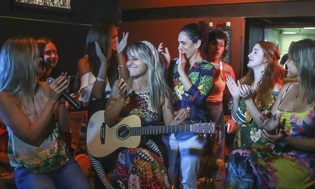 A cantora e produtora musical Tay Dantas (ao violão) comanda a noite de karaokê no Vintage Wine Bar, na Barra Foto: Marcelo Regua / Agência O Globo