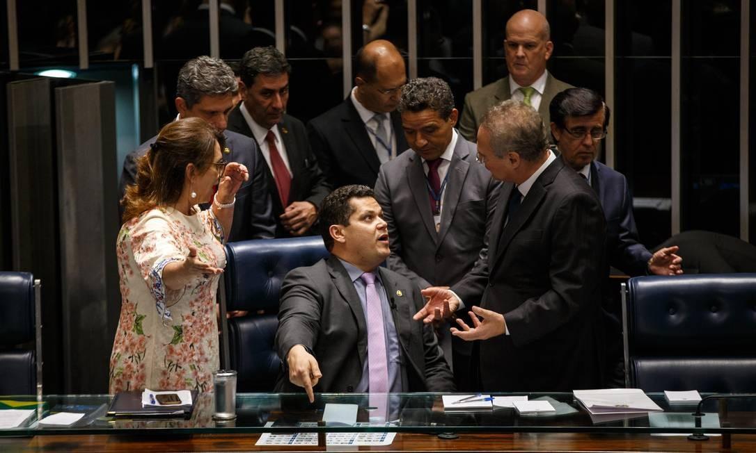Ainda no primeiro dia, o candidato Davi Alcolumbre (sentado), que acabaria se elegendo, presidiu a mesa. A decisão causou protestos entre opositores, em especial a senadora Kátia Abreu (esquerda) que chegou a pegar para si a pasta da sessão Foto: Daniel Marenco / Agência O Globo