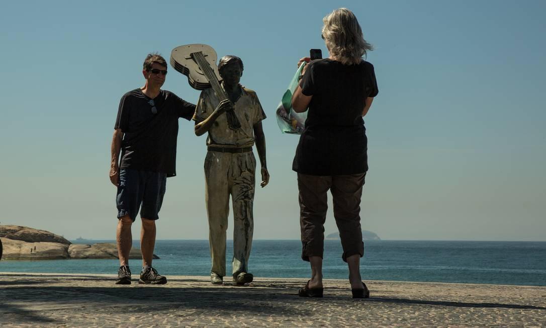 Cariocas e turistas podem tirar uma fotografia ao lado da estátua do cantor e compositor Tom Jobim, no Arpoador. Registro quase sempre vai para as redes Foto: Brenno Carvalho / Agência O Globo