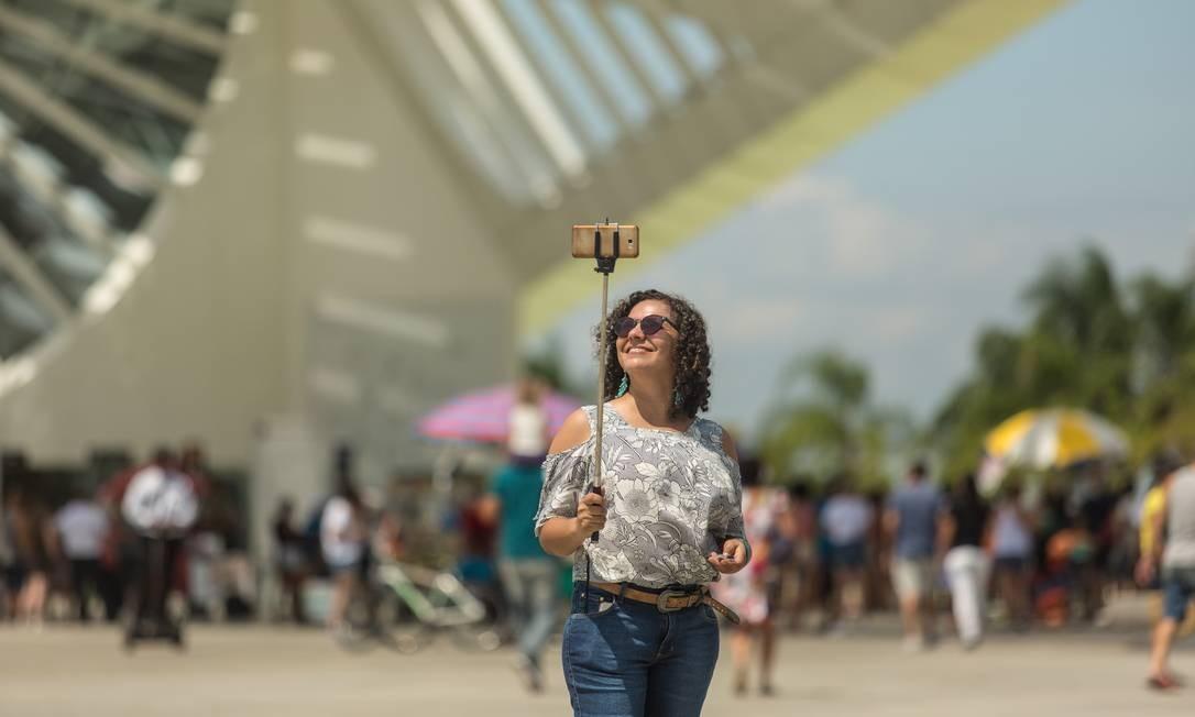 Jovem posa sorridente e mostra-se satisfeita com suas selfies tendo o Museu do Amanhã ao fundo Foto: Brenno Carvalho / Agência O Globo