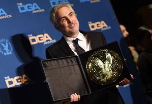O diretor Alfonso Cuarón, de 'Roma', com o seu prêmio do Directors Guild Of America (DGA) Foto: VALERIE MACON / AFP