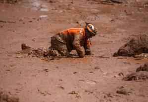Soldado dos Bombeiros entrenta o terreno instável por conta da lama em busca de sobreviventes Foto: Daniel Marenco / Agência O Globo