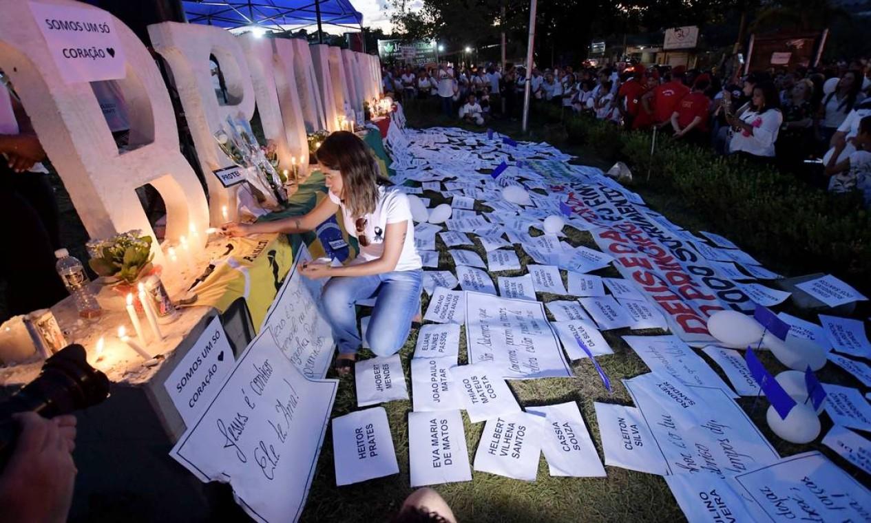 Um altar em homenagem às vítimas foi montado no letreiro com o nome de Brumadinho. Na foto, uma mulher acende uma vela durante um ato em memória das vítimas. Foto: WASHINGTON ALVES / REUTERS