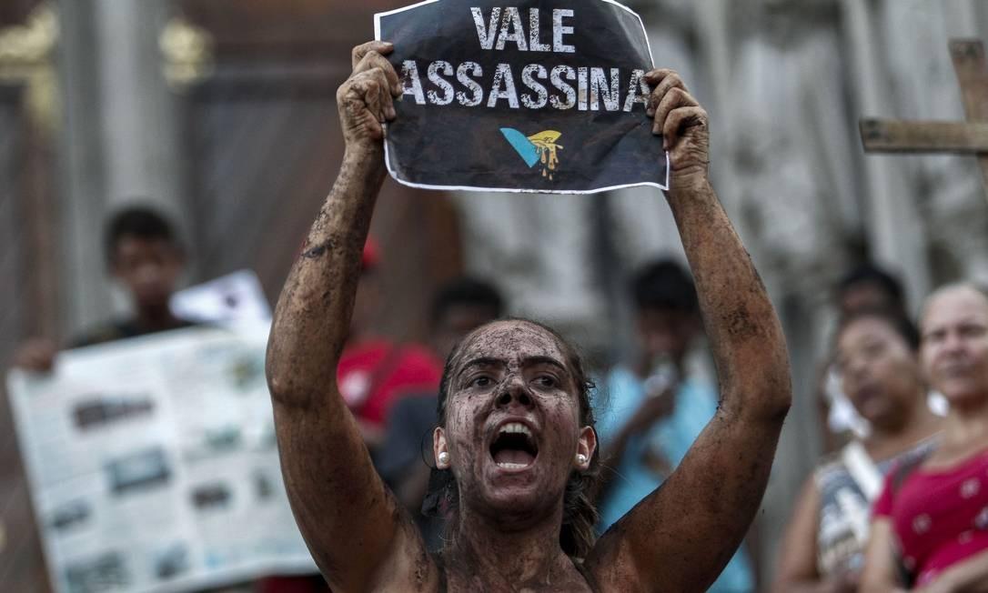 Manifestantes se sujaram de lama para protestar contra a Vale durante um protesto em frente à Catedral da Sé, em São Paulo. Também houve manifestação em frente ao prédio da mineradora no Rio. Foto: MIGUEL SCHINCARIOL / AFP