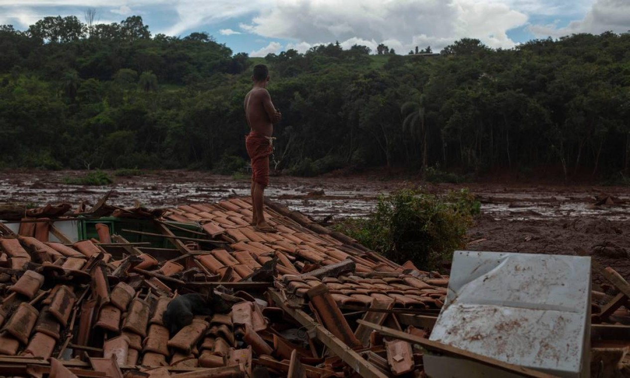 Emerson dos Santos, 30 anos, ficou em pé no telhado da casa de sua família para observar o rastro de destruição deixado pelo tsunami de lama que saiu da barragem da Vale. Foto: MAURO PIMENTEL / AFP