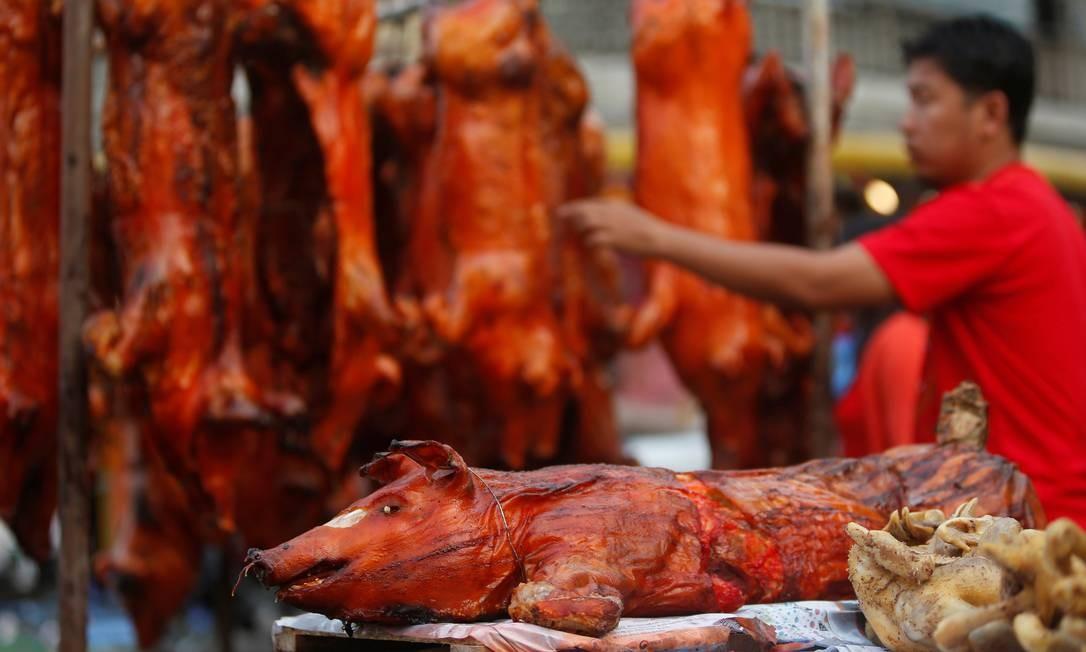 Homem compra porcos assados na rua antes da chegada do Ano Novo Chinês em Phnom Penh, no Camboja; país celebra nesta terça a chegada do Ano do Porco Foto: SAMRANG PRING / REUTERS