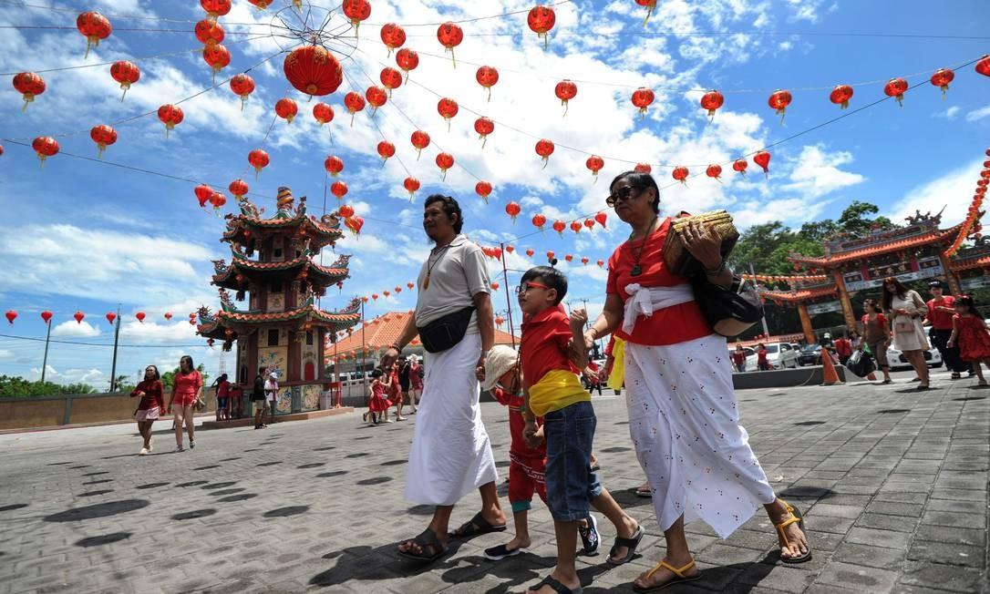 Tailandeses usam trajes tradicionais para rezar no primeiro dia do Ano Novo Chinês Foto: SONNY TUMBELAKA / AFP