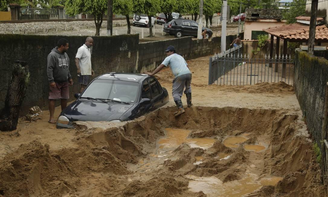 Após desabamento de encosta na estrada RJ-14, no distrito de Muriqui, em Mangaratiba, veículo foi engolido pela lama próximo ao quintal de uma casa Foto: Gabriel de Paiva / Agência O Globo
