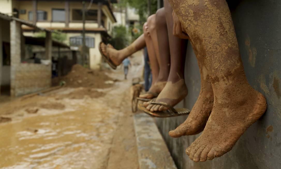 Dos muros de suas casas, crianças observam o rio de lama passar na frente de suas casas Foto: Gabriel de Paiva / Agência O Globo