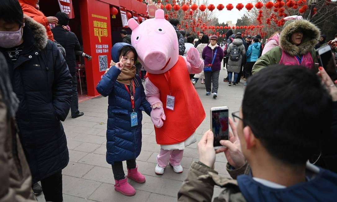 Garota chinesa posa com Peppa Pig: Ano do Porco fez personagem bombar no país Foto: GREG BAKER / AFP