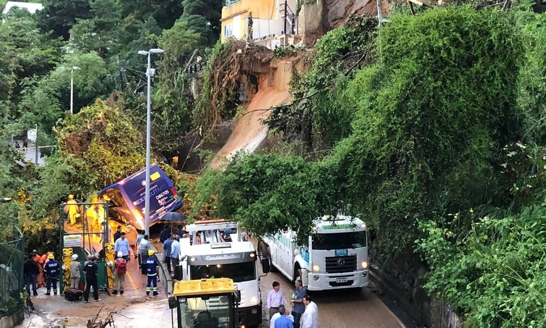 Ônibus ficou parcialmente soterrado com o deslizamento de parte da encosta do Morro do Vidigal, na Avenida Niemeyer. Segundo relato do motorista, duas pessoas ficaram presas dentro do veículo Foto: AOG