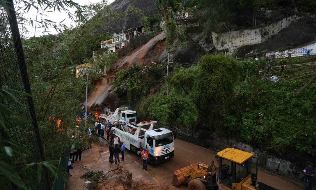 Bombeiros tiveram que serrar parte das árvores para conseguir acessar o ônibus que foi soterrado por parte da encosta do Vidigal. Os socorristas ainda não conseguiram entrar no veículo para retirar duas pessoas que ainda estão presas Foto: Marcia Foletto / Agência O Globo