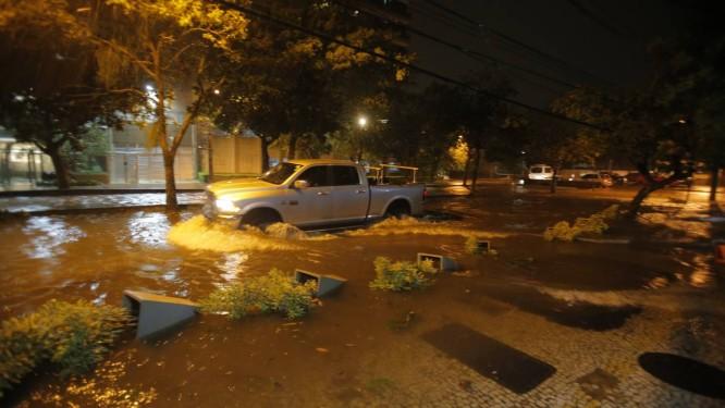 Carro tenta atravessar a Avenida Lineu de Paula Machado, na Lagoa: maior parte dos serguros cobre alagamento Foto: Alexandre Cassiano / Alexandre Cassiano