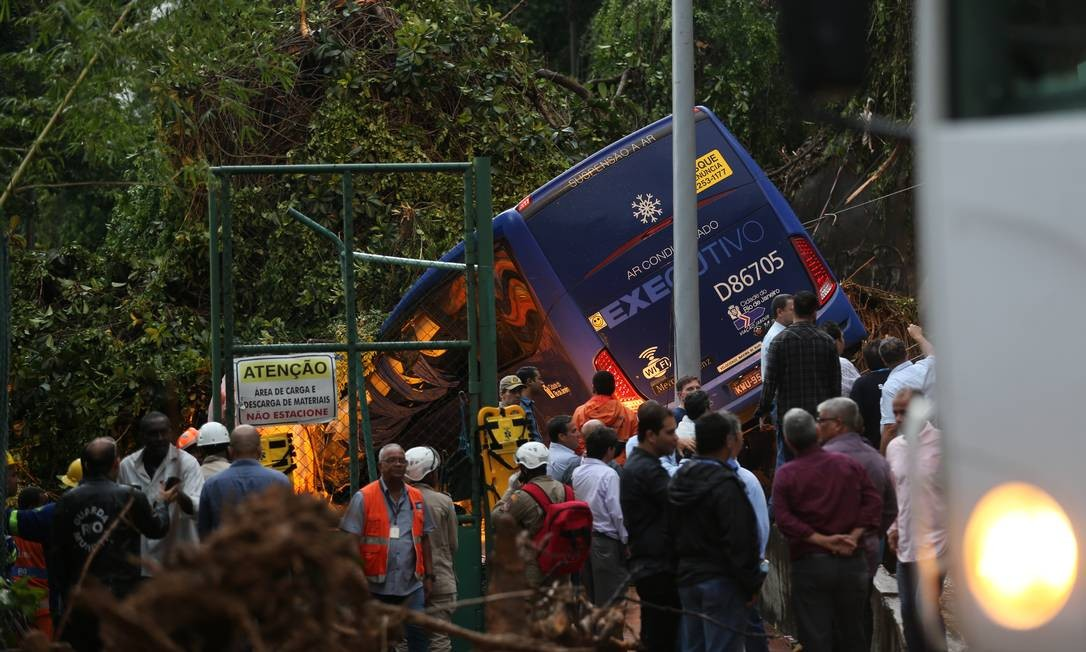 Várias equipes trabalham para a retirada de duas pessoas que o motorista afirma terem ficado dentro do ônibus Foto: Marcia Foletto / Agência O Globo