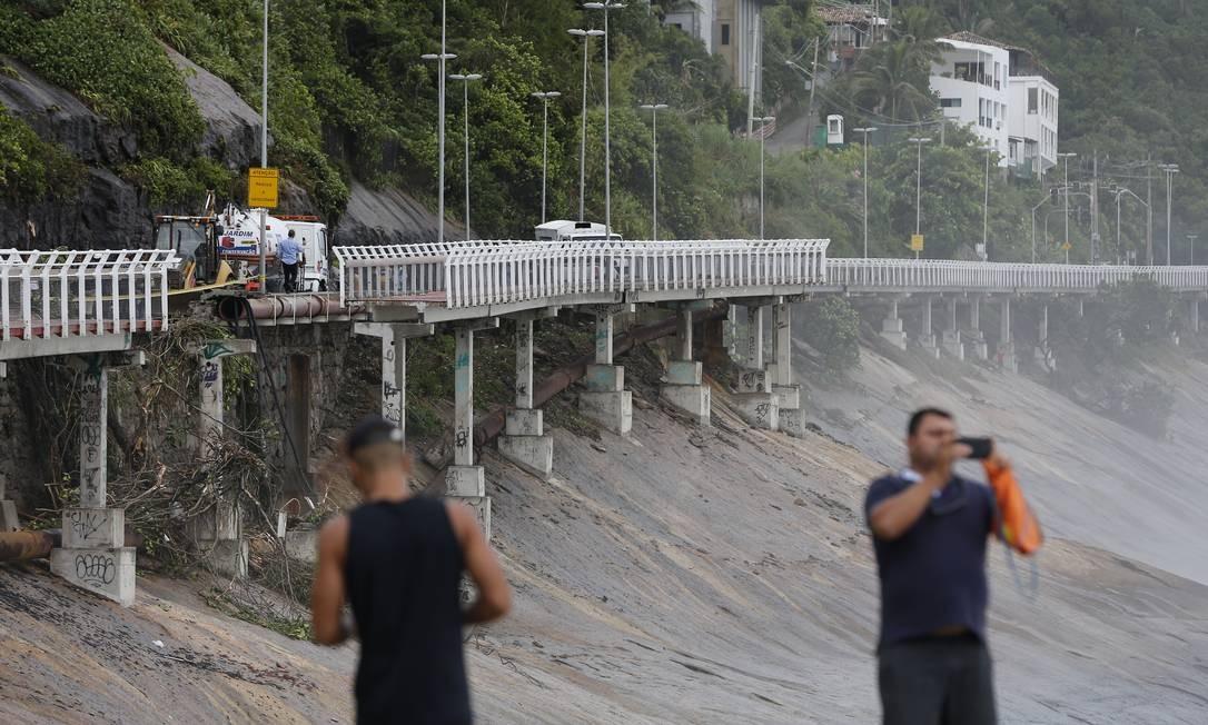 Pedestres fotografam os estragos causados pelo deslizamento de terra na avenida Niemeyer tendo ao fundo parte da ciclovia que despencou Foto: Pablo Jacob / Agência O Globo