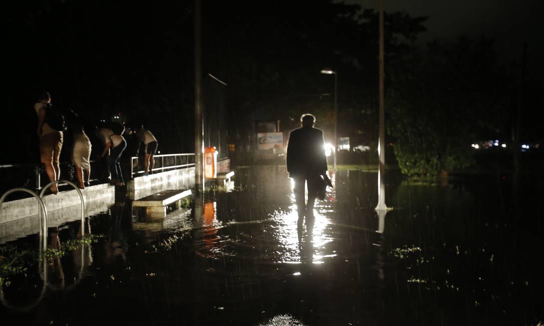 Homem caminha à noite pela Avenida Borges de Medeiros, alagada pela chuva Foto: Alexandre Cassiano / Alexandre Cassiano