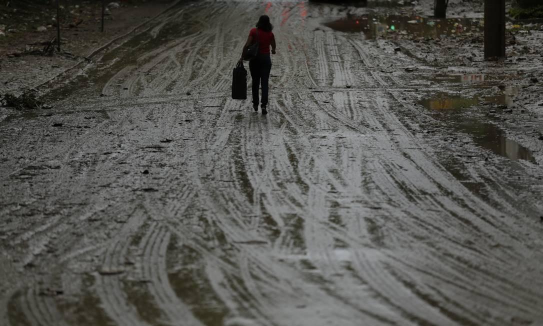 Na manhã desta quinta-feira, uma mulher caminha pela Estrada da Gávea, na altura de São Conrado. A via ficou tomada pela lama devido ao temporal que atingiu a cidade Gabriel Paiva / Agência O Globo