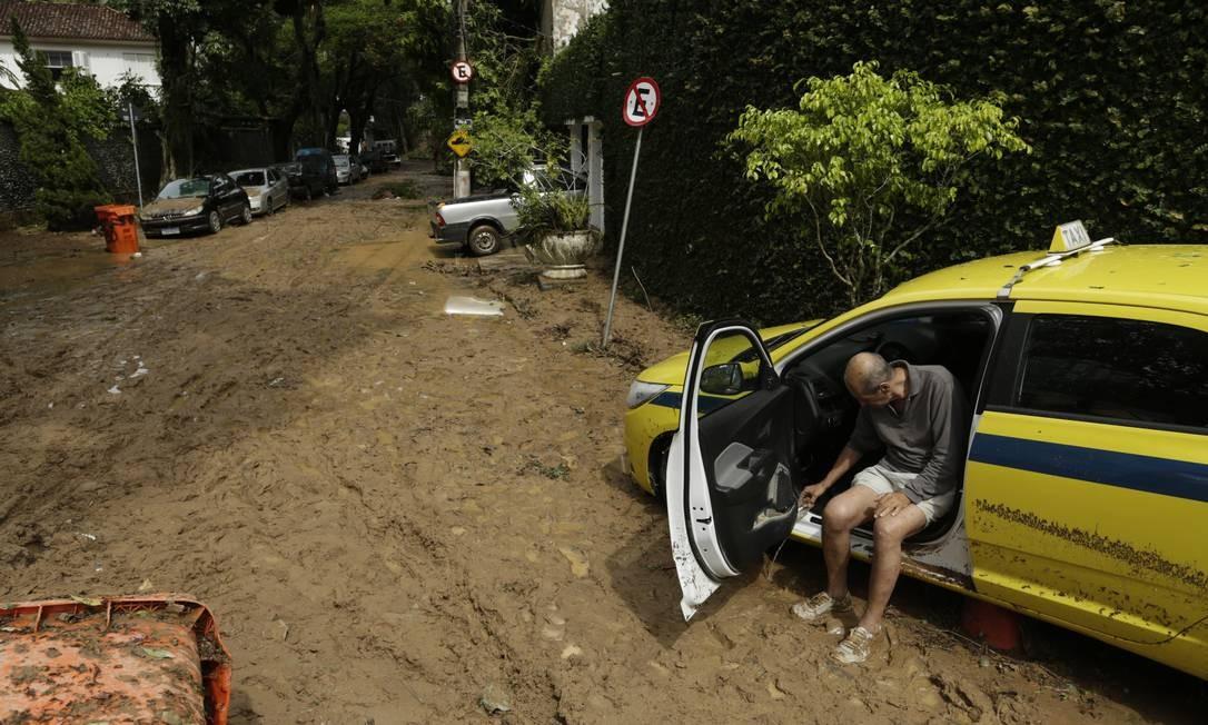 Em São Conrado, na Rua Golf Club, taxista tira a água do carro com um copinho | Gabriel Paiva / Agência O Globo