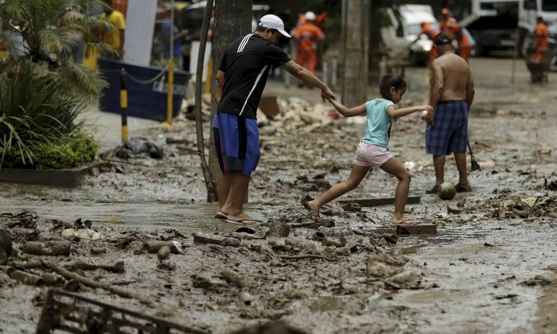 Na Estrada da Gávea, homem caminha com uma criança sobre a lama deixada pelo temporal | Gabriel de Paiva / Agência O Globo