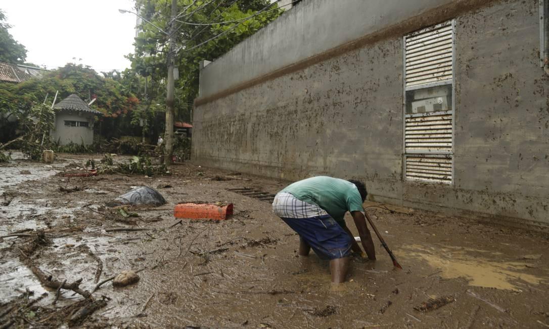Homem tenta desobstruir uma saída de água na Rua Julieta Niemeyer | Gabriel Paiva / Agência O Globo