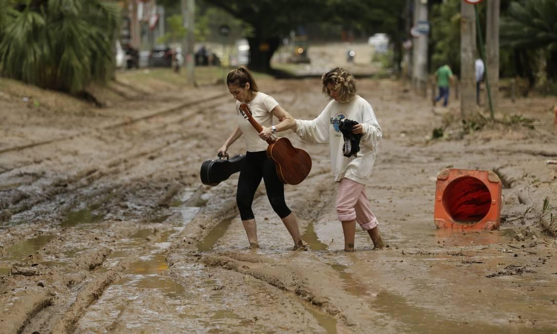Duas mulheres caminham na lama na Estrada do Joá | Gabriel Paiva / Agência O Globo