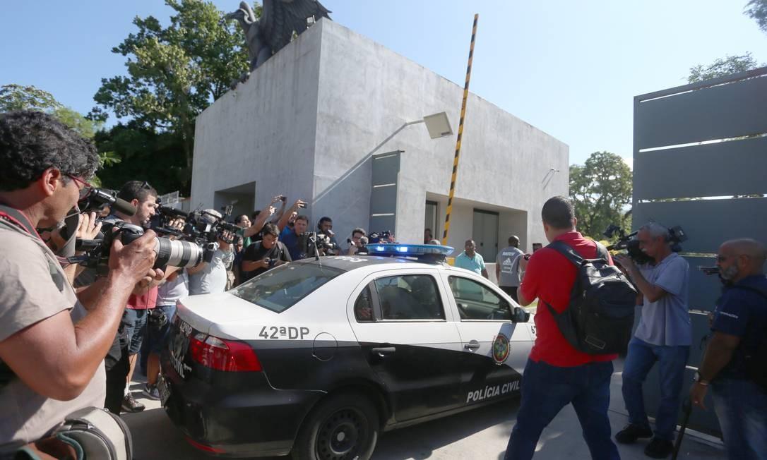 Cercado pela imprensa, carro da Polícia Civíl chega para as investigações no CT Ninho do Urubu Foto: Fabiano Rocha / Agência O Globo
