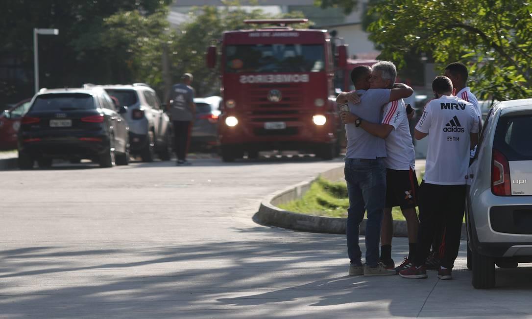 Comovidas, pessoas se abraçam enquanto esperam por informações em frente ao centro de treinamento do Flamengo | Foto: RICARDO MORAES / REUTERS