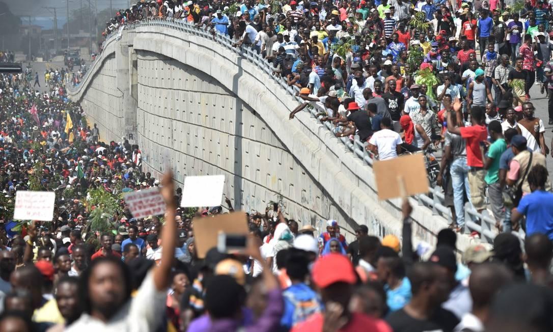 Multidão foi convocada pela oposição para sair às ruas em várias cidades, mas não há figura de líder dos protestos por enquanto; na foto, manifestantes em Porto Príncipe Foto: HECTOR RETAMAL / AFP