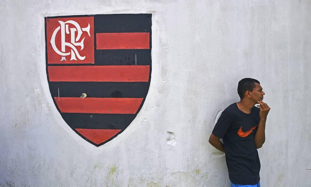 Homem ao lado do escudo do Clube de Regatas do Flamengo, do lado de fora do alojamento que pegou fogo Foto: CARL DE SOUZA / AFP