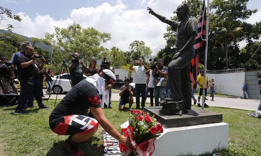 Homem faz homenagem às vítimas do incêndio pondo flores ao pé do monumento de George Helal, que dá nome ao CT do clube Rubro-Negro   Foto: Pablo Jacob / Agência O Globo