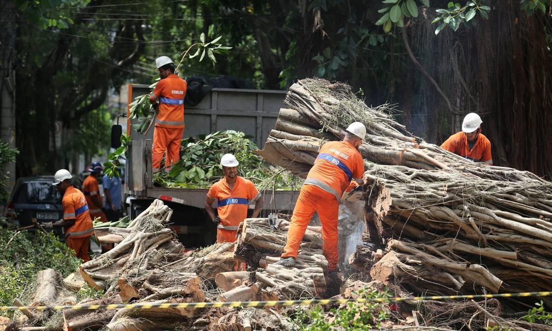 Garis cortam árvore que caiu sobre os fios na rua Maria Eugênia no Humaitá Foto: Guilherme Pinto / Agência O Globo