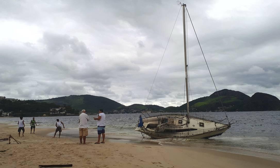 Barco que ficou à deriva na Baía de Guanabara após a forte chuva da noite de quarta-feira amanheceu na Praia de Icaraí Foto: Foto do leitor Leonardo Silva