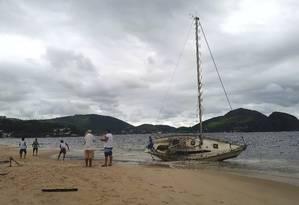 Barco que ficou à deriva na Baía de Guanabara após a forte chuva da noite de quarta-feira amanheceu na Praia de Icaraí. Foto: Foto do leitor Leonardo Silva