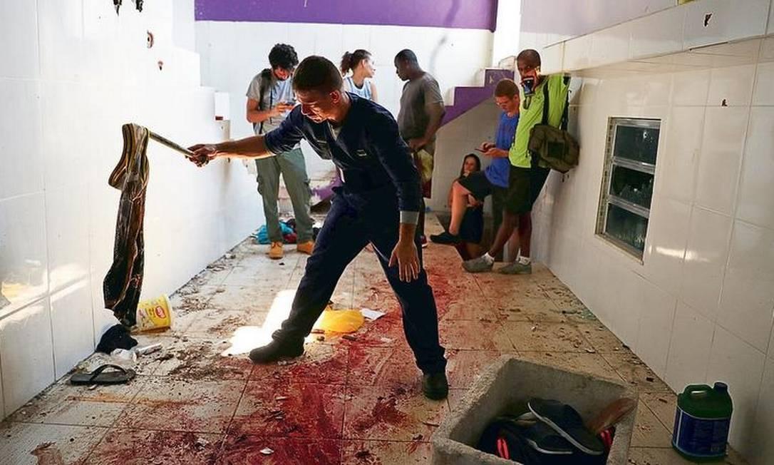 Um perito recolhe uma roupa na casa em que dez pessoas foram mortas, no Morro do Fallet. Segundo a PM, as vítimas haviam entrado em confronto com o Batalhão de Choque, mas moradores denunciam execução Foto: Pilar Olivares / REUTERS